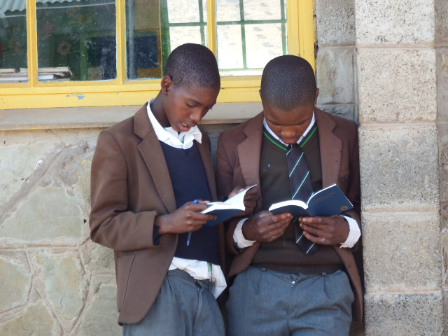 Two students read their copies of God's Word after a distribution at a Lesotho school.