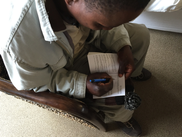 A young man acknowledges Jesus as his Lord and Savior as he signs the decision page in his New Testament after receiving a Scripture during the 2015 Lesotho International Scripture Blitz.
